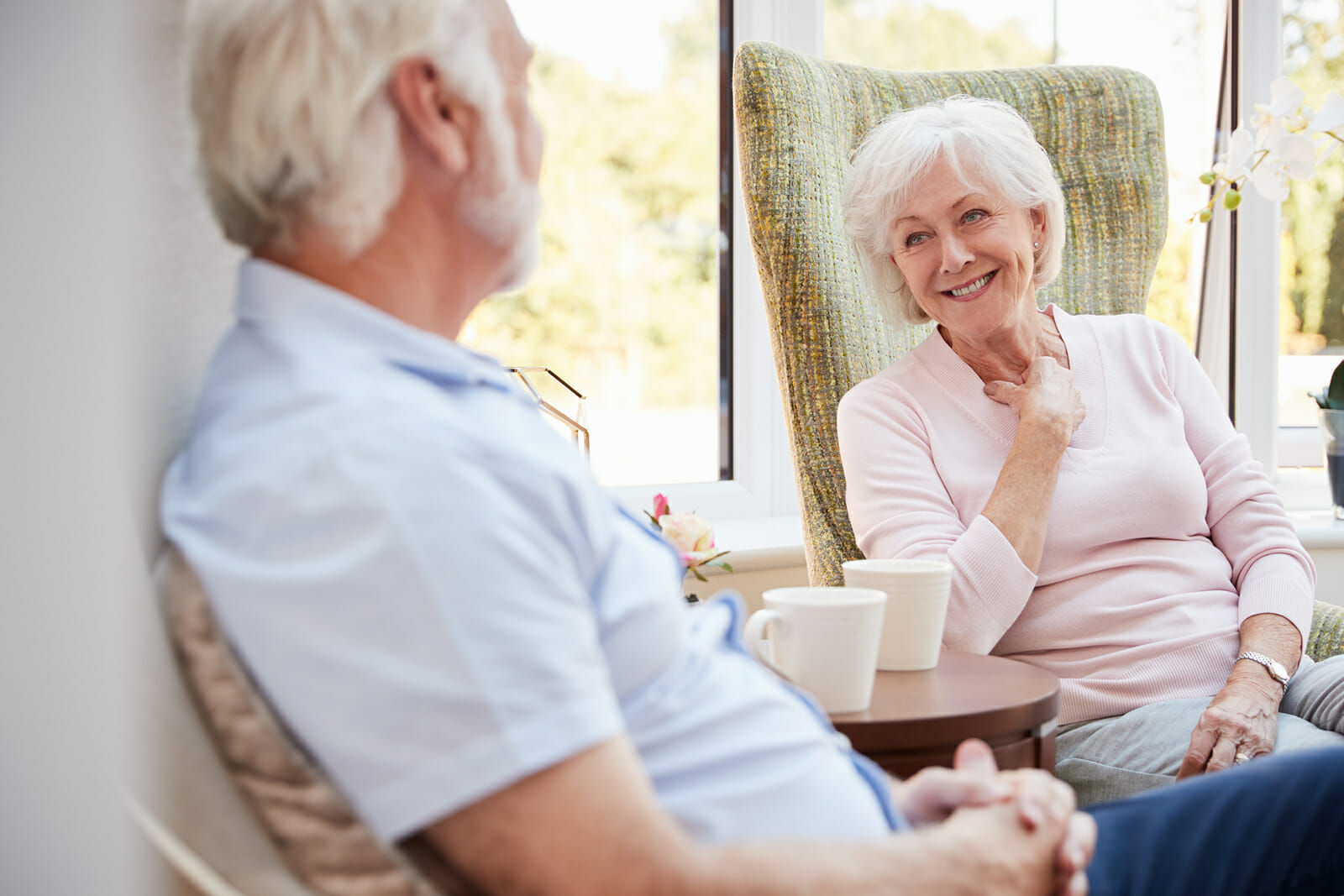 Senior Couple Sitting In Chairs And Chatting